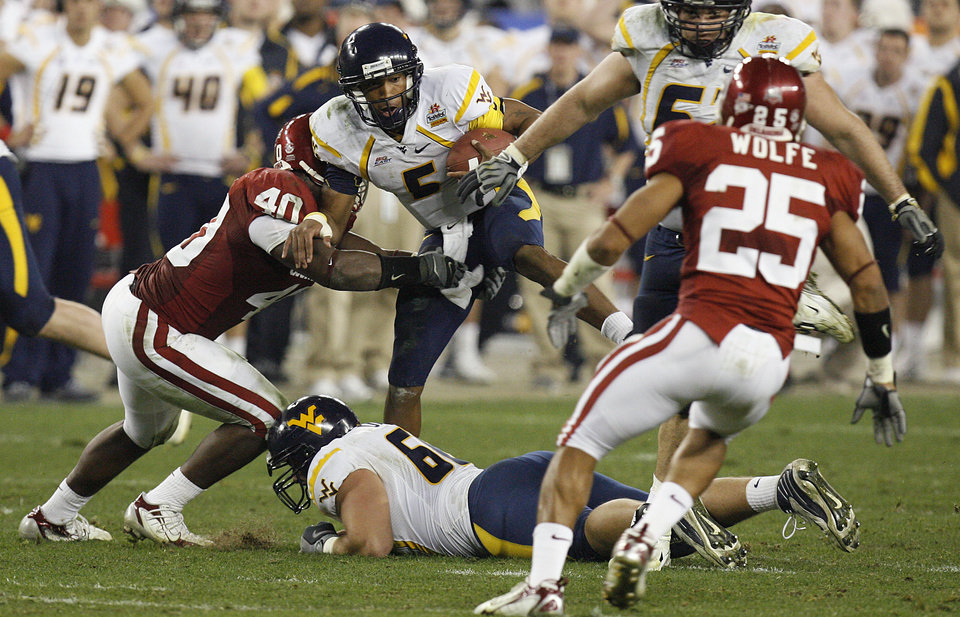 Photo - West Virginia's Patrick White (5) is brought down by Oklahoma's Curtis Lofton (40) during the first half of the Fiesta Bowl college football game between the University of Oklahoma Sooners (OU) and the West Virginia University Mountaineers (WVU) at The University of Phoenix Stadium on Wednesday, Jan. 2, 2008, in Glendale, Ariz. 