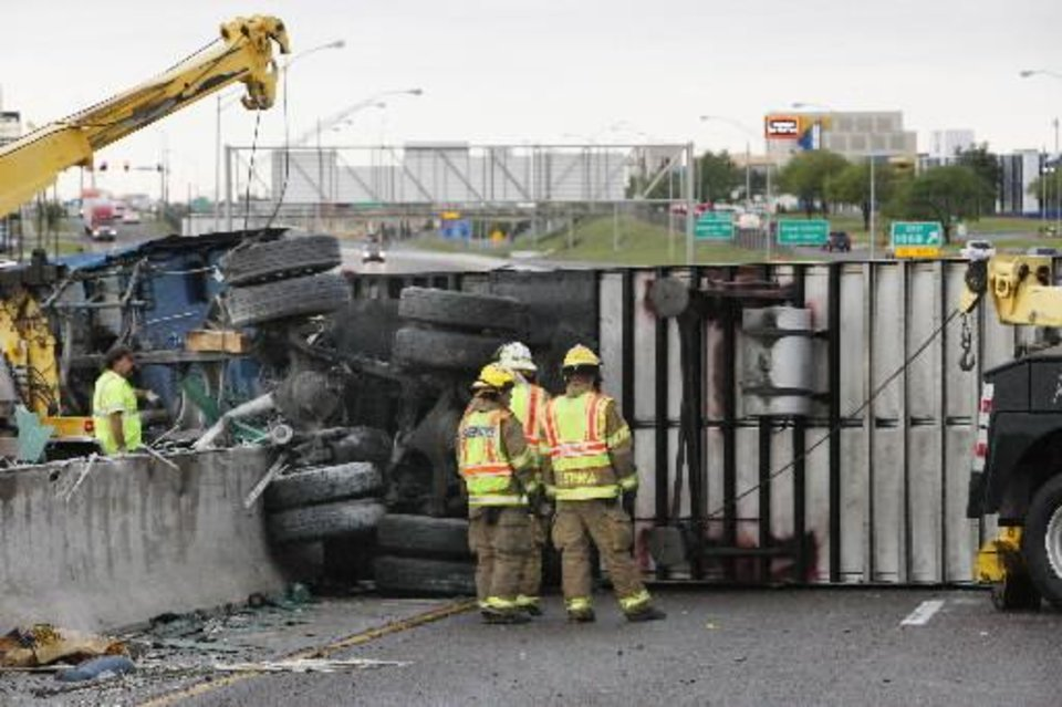 A wrecker operator and Midwest City firemen look at removing a semi cab and trailer from the center wall where it overturned on I-40 just west of Air Depot in Midwest City Thursday, May 9, 2013. The wreck shut down both east and west bound I-40. Photo by Paul B. Southerland, The Oklahoman