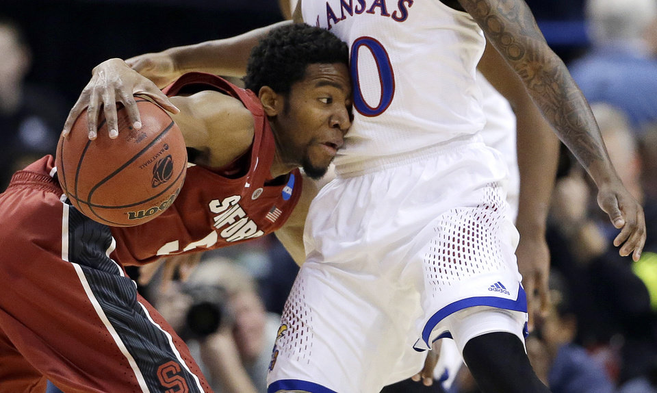 Photo - Stanford's Chasson Randle, left, tries to maneuver around Kansas' Naadir Tharpe, right, during the first half of a third-round game of the NCAA college basketball tournament Sunday, March 23, 2014, in St. Louis. (AP Photo/Jeff Roberson)