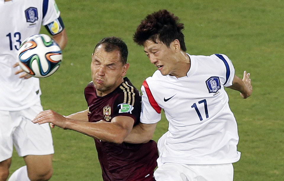 Photo - Russia's Sergei Ignashevich, left, and South Korea's Lee Chung-yong (17) go for a header during the group H World Cup soccer match between Russia and South Korea at the Arena Pantanal in Cuiaba, Brazil, Tuesday, June 17, 2014. (AP Photo/Thanassis Stavrakis)