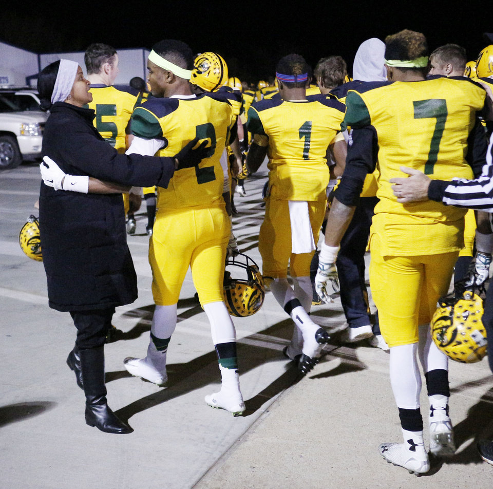 Photo - Patricia Henderson encourages her son Jacques Henderson, #2 and the team as they head in at half-time during the high school football playoff between McAlester and Lawton MacArthur at Choctaw stadium, November 28, 2014. Photo by Doug Hoke, The Oklahoman
