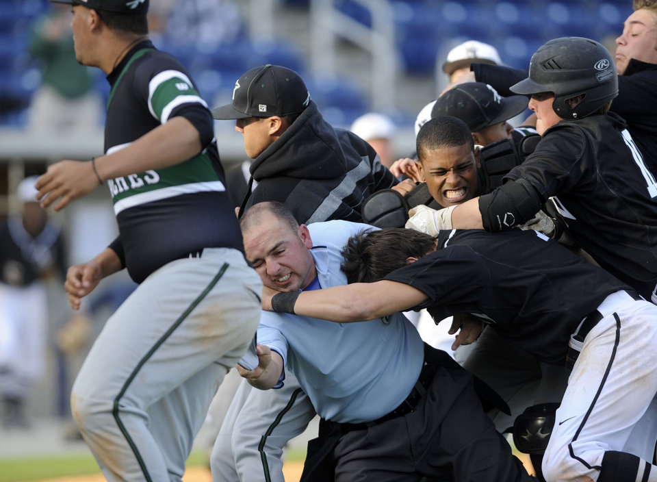 A brawl breaks out at on the field at Maritime Park Stadium Wednesday during a game between Norman North and Arlington as part of the 2013 Aggie Classic. PHOTO BY PENSACOLA NEWS JOURNAL <strong>Ben Twingley/btwingley@pnj.com - Ben Twingley/btwingley@pnj.com</strong>