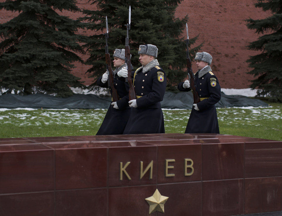 "Photo - Kremlin honor guards walk past a monument marking Kiev's role in World War II, at the Kremlin wall in Moscow, Russia, Wednesday, Feb. 19, 2014. Russia on Wednesday blamed the West for the escalation of violence in Ukraine's capital and said that it viewed the developments in Kiev as a ""coup attempt."" (AP Photo/Alexander Zemlianichenko)"
