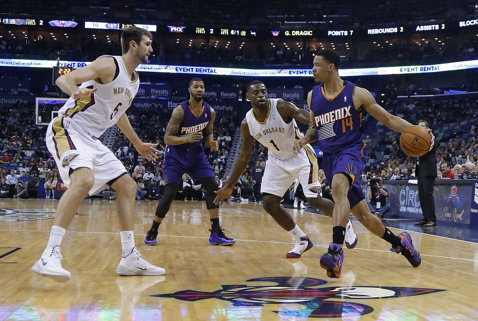 Photo - Phoenix Suns guard Gerald Green (14) drives to the basket in front of New Orleans Pelicans forward Tyreke Evans (1) and into Pelicans center Jeff Withey (5) as Suns forward Marcus Morris (15) looks on in the first half of an NBA basketball game in New Orleans, Wednesday, April 9, 2014. (AP Photo/Bill Haber)