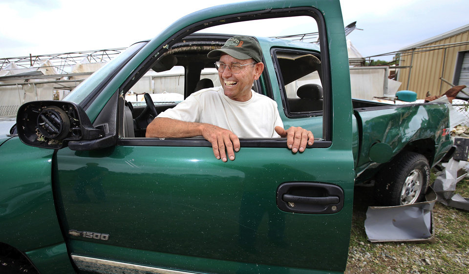 Larry Jernigan, 62, of Shawnee, laughs when recalling events of Monday night when he rode out a tornado inside his 1999 pickup truck in front of his cabinet shop on State Highway 99 in Seminloe. He hunkered down in the front seat as the twister moved his truck about 10 feet. Jernigan's truck had all the windows blown out and the body received heavy damage. He escaped without injury.    Photo by Jim Beckel, The Oklahoman