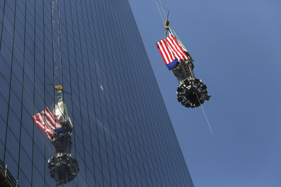 Photo - The final piece of the spire is hoisted to the roof of One World Trade Center in New York, Thursday, May 2, 2013. The piece will be attached to the spire at a later date, capping off the tower at 1,776 feet. (AP Photo/Mark Lennihan)