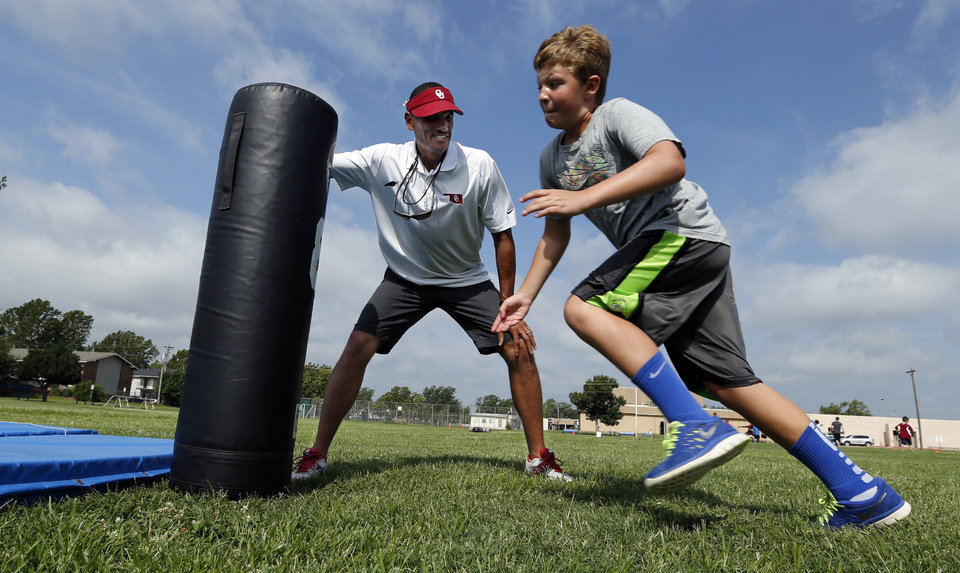 Photo - University of Oklahoma's (OU) co-offensive coordinator Jay Norvell holds a blocking dummy for Bryce Christian, 9, as he hosts his annual youth camp at Whittier Middle School on Tuesday, June 17, 2014 in Norman, Okla.  Photo by Steve Sisney, The Oklahoman