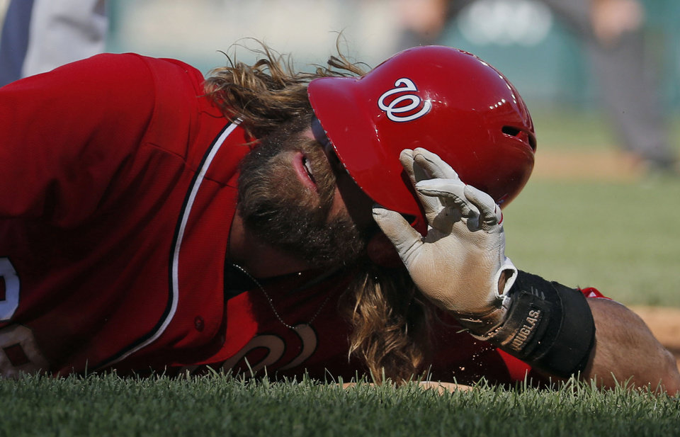 Photo - Washington Nationals' Jayson Werth asks for timeout after sliding safely into third base during the third inning of a baseball game against the Chicago Cubs at Nationals Park, Saturday, July 5, 2014, in Washington. (AP Photo/Alex Brandon)