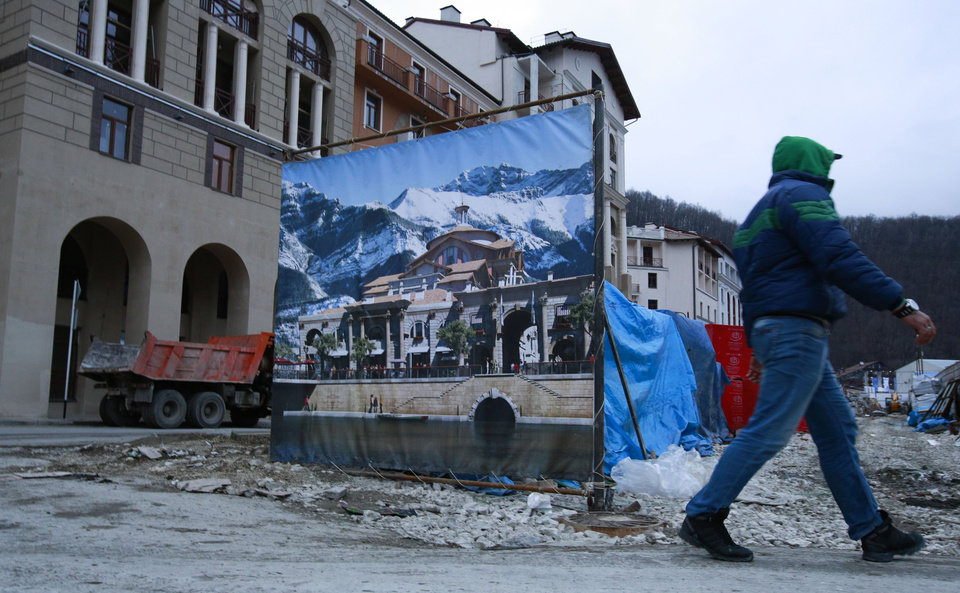 Photo - A worker enters a construction site behind a decorate fence next to accommodation for the Sochi 2014 Winter Olympics, Saturday, Feb. 1, 2014, in Krasnaya Polyana, Russia. According to the Sochi Olympic organizing committee, only six of the nine media hotels in the mountain area are fully operational. The accommodation for athletes, however, has not been affected by the problems. (AP Photo/Gero Breloer)