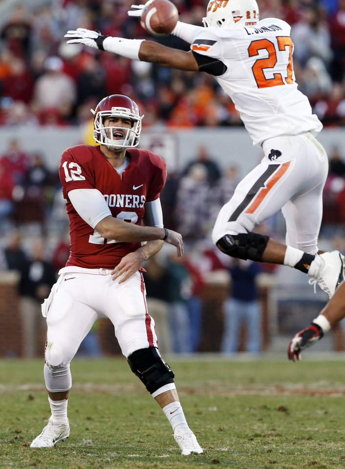 Photo - Oklahoma's Landry Jones (12) throws as Oklahoma State's Lyndell Johnson (27) tries to block the ball during the second half of the Bedlam college football game in which  the University of Oklahoma Sooners (OU) defeated the Oklahoma State University Cowboys (OSU) 51-48 in overtime at Gaylord Family-Oklahoma Memorial Stadium in Norman, Okla., Saturday, Nov. 24, 2012. Photo by Steve Sisney, The Oklahoman