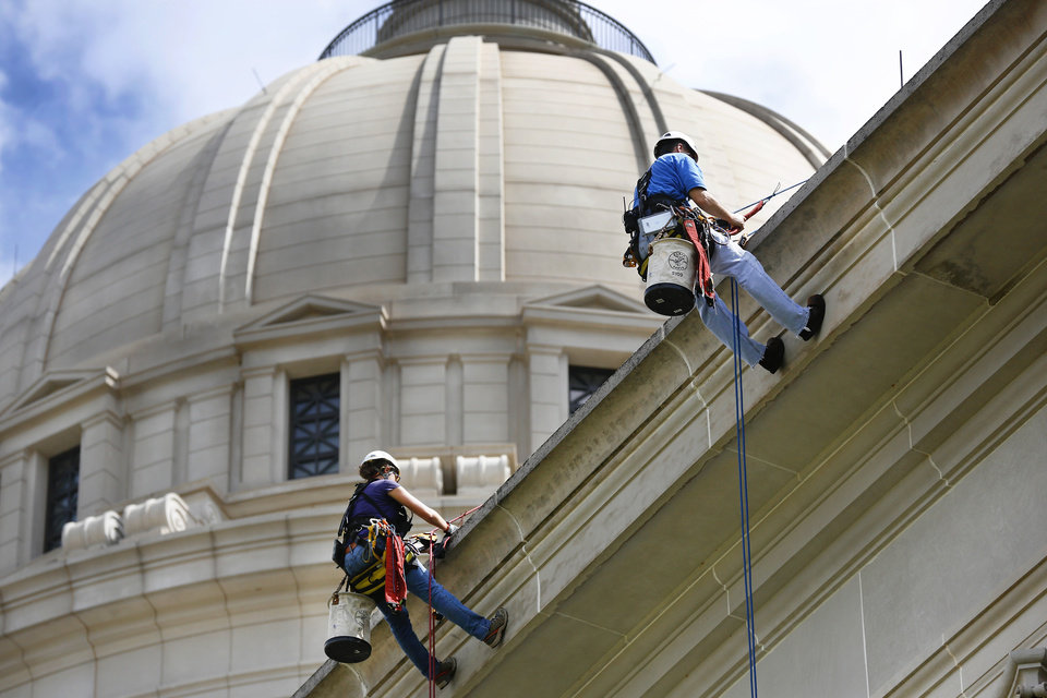 Photo - Sarah Sinusas, left, and Steve Naggatz, engineers with WJE Architects and Engineers, hang nearly 60 feet above the ground as they step off the ledge of the state Capitol during an inspection of the building in September. The Oklahoma Supreme Court on Monday struck down a legal challenge to the bond issue that will pay for repairs to the Capitol.  PHOTO BY JIM BECKEL, THE OKLAHOMAN ARCHIVES  Jim Beckel -  THE OKLAHOMAN