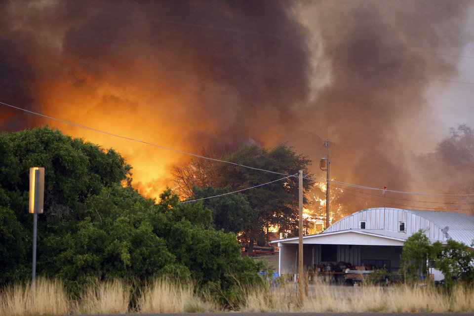 Photo - Homes burn as the Yarnell Hill Fire approaches Glenn Ilah on Sunday, June 30, 2013 near Yarnell, Ariz. The fire started Friday and picked up momentum as the area experienced high temperatures, low humidity and windy conditions. It has forced the evacuation of residents in the Peeples Valley area and in the town of Yarnell. (AP Photo/The Arizona Republic, David Kadlubowski)