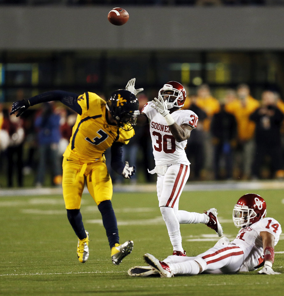 Oklahoma's Javon Harris (30) intercepts a pass intended for West Virginia's Stedman Bailey (3) after it was tipped by Oklahoma's Aaron Colvin (14) in the second quarter during a college football game between the University of Oklahoma and West Virginia University on Mountaineer Field at Milan Puskar Stadium in Morgantown, W. Va., Nov. 17, 2012. Photo by Nate Billings, The Oklahoman