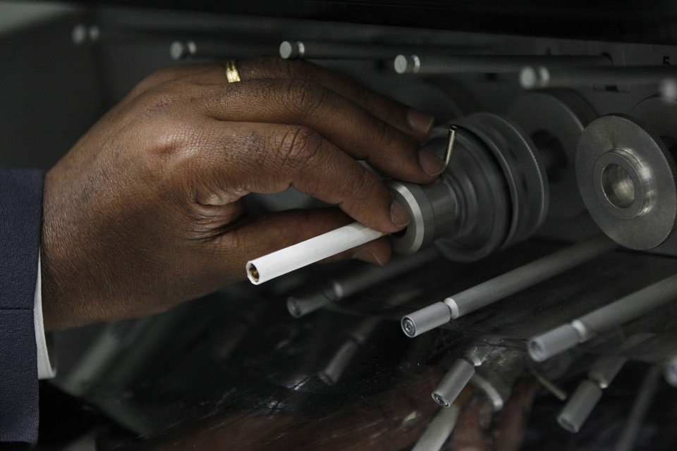 In this Thursday, April 19, 2012 photo, a cigarette is positioned in a mainstream linear 20-port smoking machine at the U.S. Department of Treasury's Alcohol and Tobacco Tax and Trade Bureau laboratory, in Beltsville, Md. The Alcohol and Tobacco Tax and Trade Bureau, which collects taxes on booze and smokes and tells the companies that produce them how to do business, is one example of the specialized government offices threatened by Washington�s current zeal for cost-cutting. (AP Photo/Charles Dharapak)
