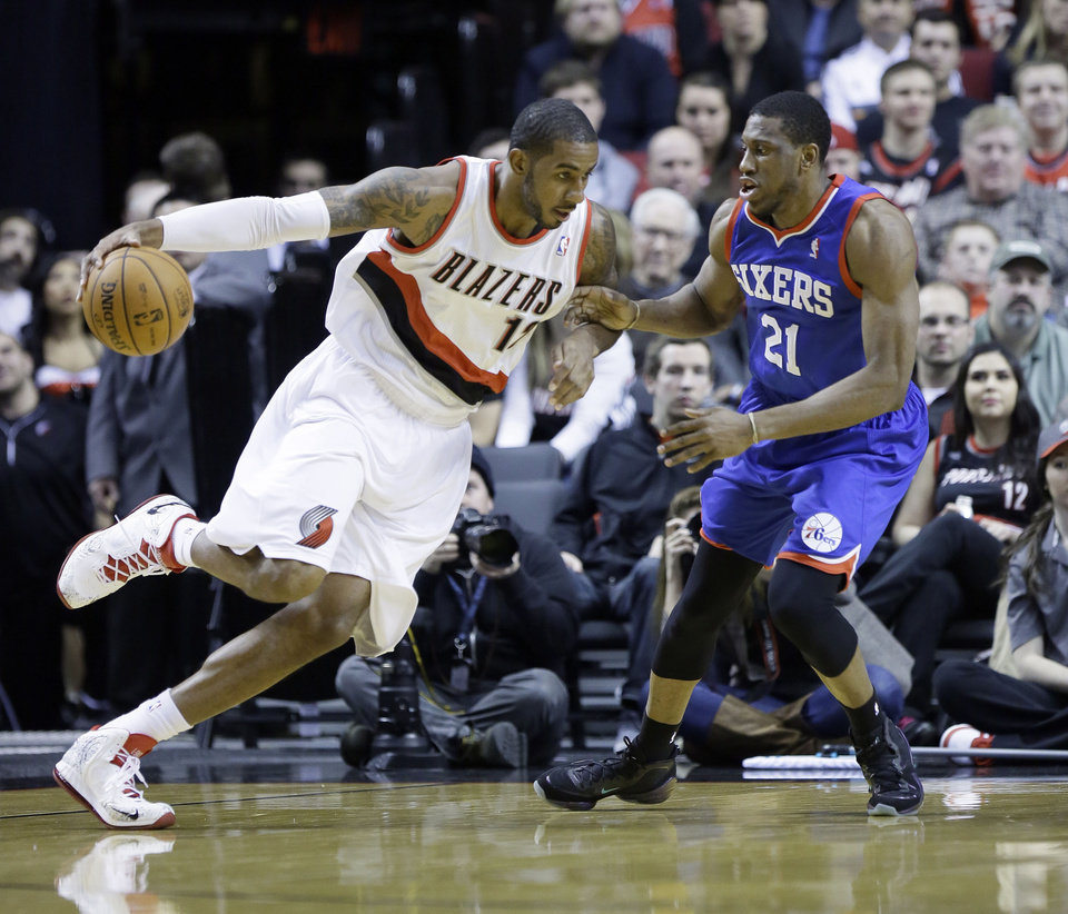 Photo - Portland Trail Blazers forward LaMarcus Aldridge, left, drives on Philadelphia 76ers forward Thaddeus Young during the first half of an NBA basketball game in Portland, Ore., Saturday, Jan. 4, 2014. (AP Photo/Don Ryan)
