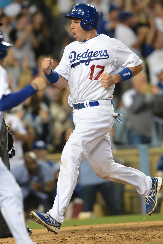 Photo - Los Angeles Dodgers' A.J. Ellis pumps his fist as scores on a three-run double by Dan Haren in the fourth inning of a baseball game against the Arizona Diamondbacks on Saturday, June 14, 2014, in Los Angeles. (AP Photo/Jayne Kamin-Oncea)