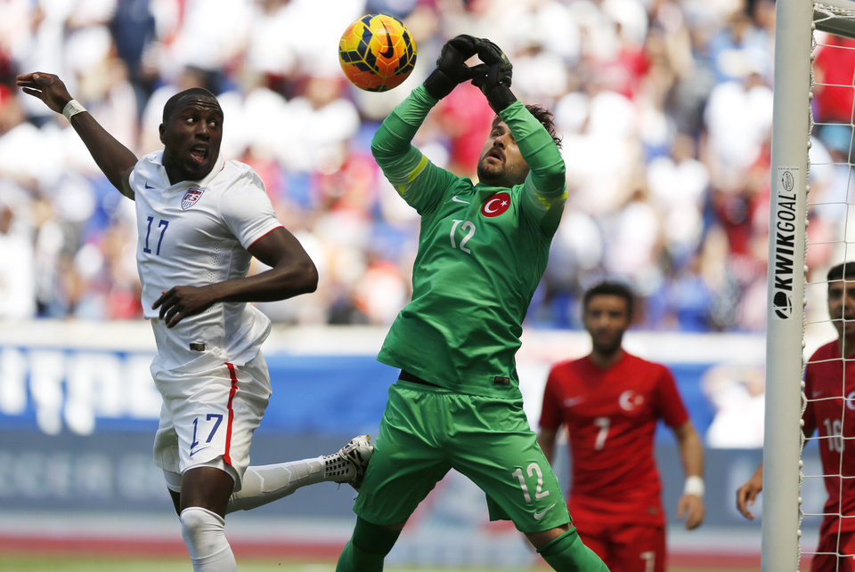 Photo - Turkey goalkeeper Onur Recep Kivrak, right, goes up for the ball as United States' Jozy Altidore attacks in the first half of an international soccer friendly, Sunday, June 1, 2014, in Harrison, N.J. (AP Photo/Julio Cortez)