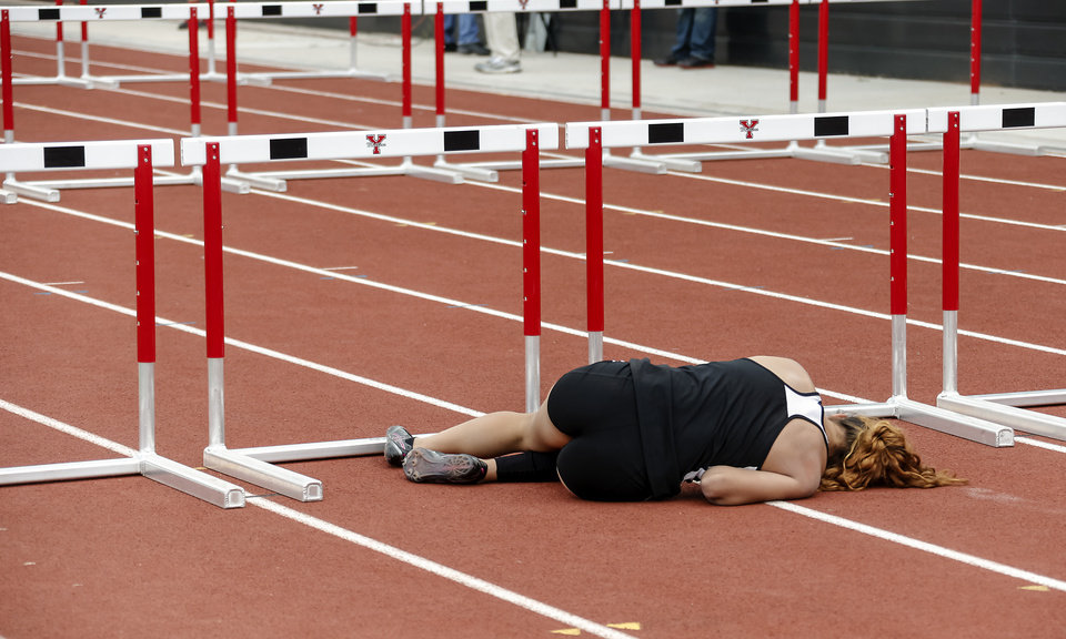 Photo - Putnam City's Schuyler Wood lies on the track after taking a fall in the 6A girls 100m hurdles during the class 5A and 6A track state championships at Yukon High School on on Friday, May 10, 2013, in Yukon, Okla.Photo by Chris Landsberger, The Oklahoman