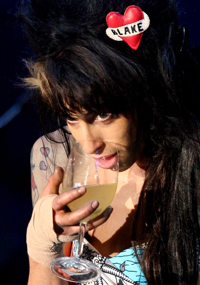 Photo - FILE - In this May 30, 2008 file photo, singer Amy Winehouse has a drink while performing to 90,000 spectators on the main stage of the Rock in Rio Lisboa music festival at the Bela Vista Park in Lisbon. Amy Winehouse, the beehived soul-jazz diva whose self-destructive habits overshadowed a distinctive musical talent, was found dead Saturday, July 23, 2011 in her London home, police said. She was 27. (AP Photo/Steven Governo, File) ORG XMIT: XDA110