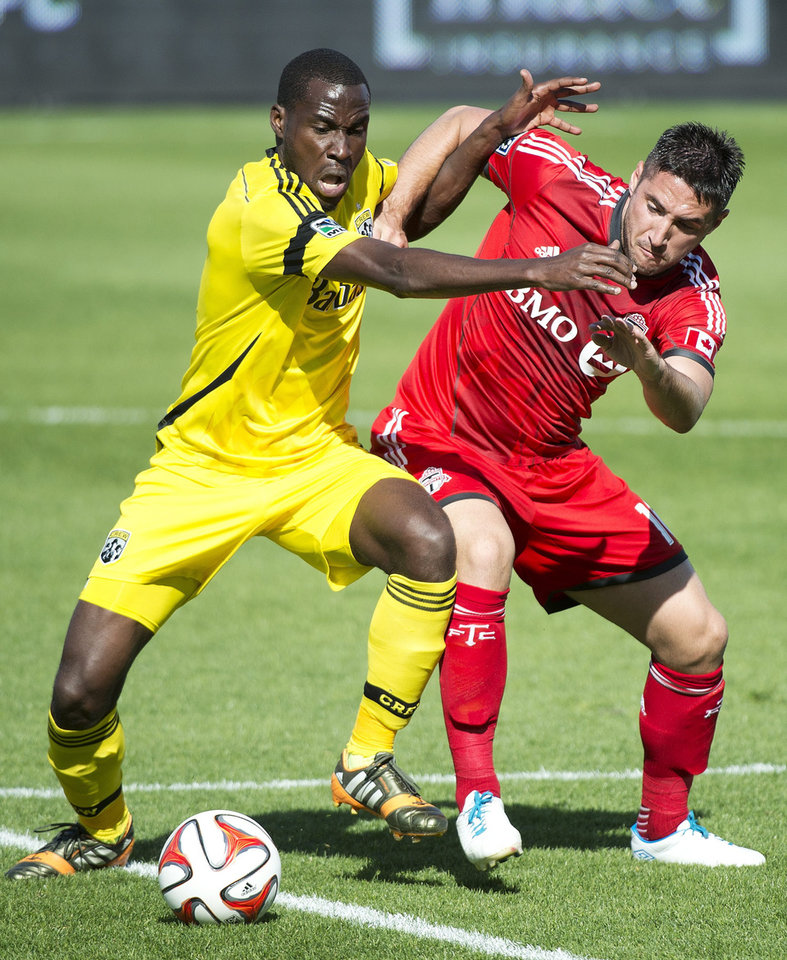 Photo - Toronto FC midefielder Brad Orr, right, vies for the ball against Columbus Crew midfielder Tony Tchani during the first half of an MLS soccer game in Toronto on Saturday, May 31, 2014. (AP Photo/The Canadian Press, Nathan Denette)