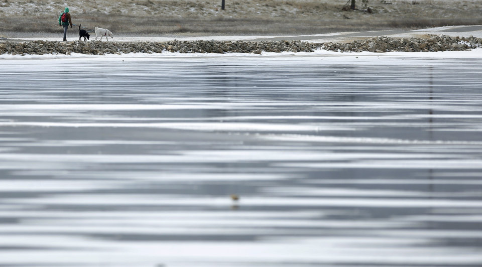Photo - A person walks dogs around the frozen pond in front of the Meridian Technology Center in Stillwater, Okla., Saturday, Feb. 13, 2021. Photo by Sarah Phipps, The Oklahoman