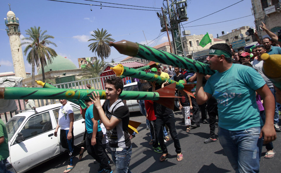 Photo - Palestinian supporters of Hamas hold representations of rockets as others chant slogans against the Israeli military action in Gaza, during a demonstration in the West Bank city of Jenin on Friday, Aug. 22, 2014. (AP Photo/Mohammed Ballas)