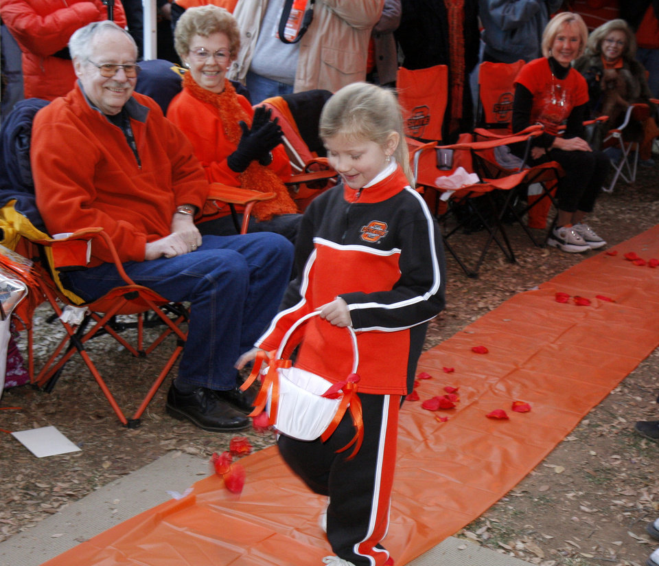 Photo - Six year old Shayn King spreads flowers pedals down the aisle at Cowboy fans Scott Stuart and Yvonne Marsh wedding before the college football game between the University of Oklahoma Sooners (OU) and Oklahoma State University Cowboys (OSU) at Boone Pickens Stadium on Saturday, Nov. 29, 2008, in Stillwater, Okla. 