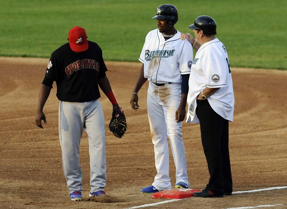 Photo - Pete Rose, right, talks with Bridgeport Bluefish's James Simmons, center, as Lancaster Barnstormers' Wilson Batista, right, stands by, Monday, June 16, 2014, in Bridgeport, Conn. Rose, banned from Major League Baseball, returned to the dugout for one day to manage the independent minor-league Bridgeport Bluefish. (AP Photo/Jessica Hill)