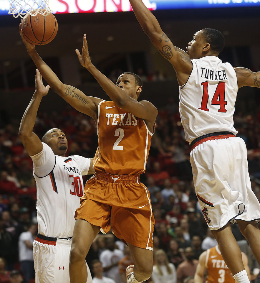 Photo - Texas' Demarcus Holland shoots between Texas Tech's Jaye Crockett (30) and Robert Turner (14) during their NCAA college basketball game in Lubbock, Texas, Saturday, Mar, 8, 2014. (AP Photo/Lubbock Avalanche-Journal, Zach Long) ALL LOCAL TV OUT