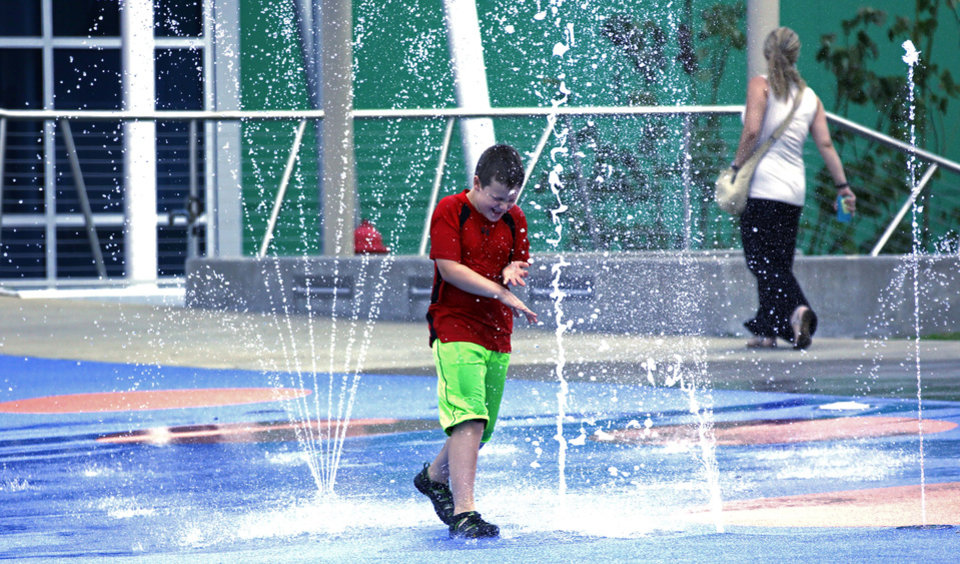 Photo - In this July 3, 2014 photograph, Clark Blair, 7, enjoys the interactive dancing waters on the path to the Mississippi Children's Museum in Jackson, Miss. The interactive hands-on facility promotes literacy, health and nutrition, learning the state's heritage and exploration of its cultural arts and key economic industries in a fun setting. (AP Photo/Rogelio V. Solis)