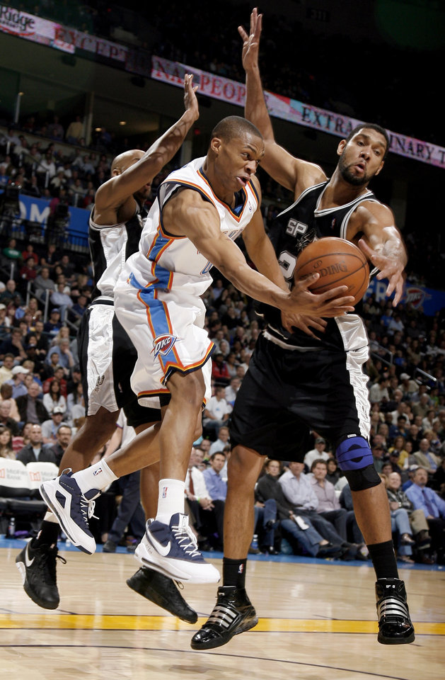 Photo - Oklahoma City's Russell Westbrook (0) passes the ball as San Antionio's Bruce Bowen (12) , left, and Tim Duncan (21) defend him during the NBA game between Oklahoma City and San Antonio, Tuesday April 7, 2009, at the Ford Center in  Oklahoma CIty. Photo by Sarah Phipps, The Oklahoma