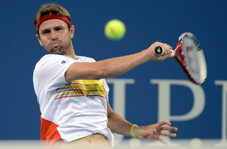 Photo -   Mardy Fish returns a shot to Gilles Simon of France in the third round of play at the U.S. Open tennis tournament, Saturday, Sept. 1, 2012, in New York. (AP Photo/Henny Ray Abrams)