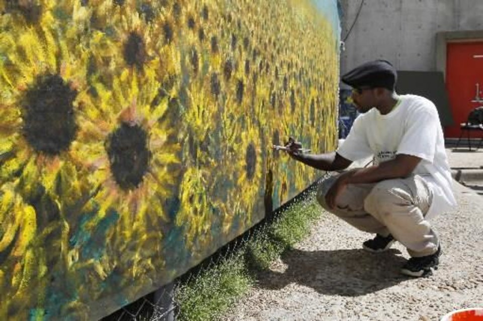 Photo -  Del City artist Andrew Akufo works on a sunflower mural during the Festival of the Arts in downtown Oklahoma City, OK, Thursday, April 25, 2013, By Paul Hellstern, The Oklahoman Archive