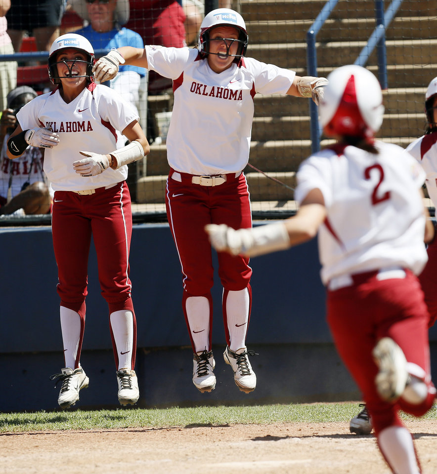 Photo - From left, OU's Destinee Martinez (00) and Callie Parsons (12) cheer for Brianna Turang (2) as she runs to home plate in the third inning during an NCAA softball game in the Women's College World Series between Oklahoma and Texas at ASA Hall of Fame Stadium in Oklahoma City, Saturday, June 1, 2013. All three Oklahoma players scored on the play. Oklahoma won 10-2 in five innings. Photo by Nate Billings, The Oklahoman