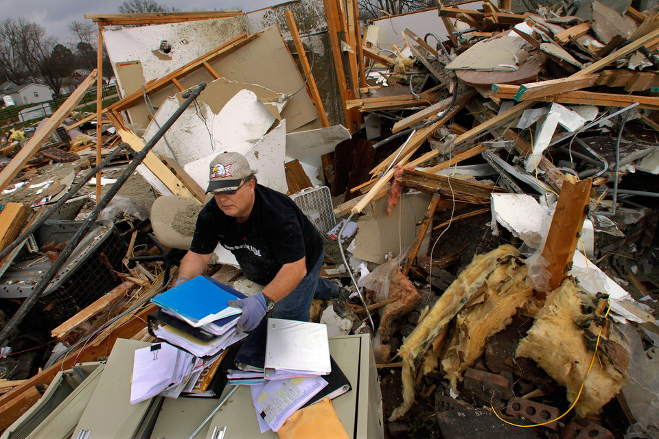 Photo -   Joe Jenkins helps salvage medical records from a destroyed senior center Friday, March 2, 2012, in Harrisburg, Ill. A pre-dawn twister flattened entire blocks of homes Wednesday as violent storms ravaged the Midwest and South. (AP Photo/Seth Perlman)