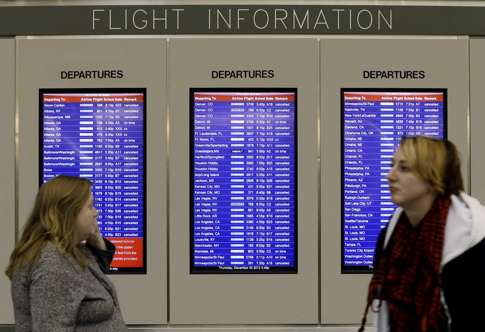 A flight information screen displays canceled flights as passenger walk at Midway airport in Chicago, Thursday, Dec. 20, 2012. The first widespread snowstorm of the season crawled across the Midwest on Thursday, with whiteout conditions stranding holiday travelers. The storm led airlines to cancel about 1,000 flights ahead of the Christmas holiday � relatively few compared to past big storms, though the number was climbing.  Southwest Airlines scratched all of its flights scheduled after 4:30 p.m. today at Midway. (AP Photo/Nam Y. Huh)