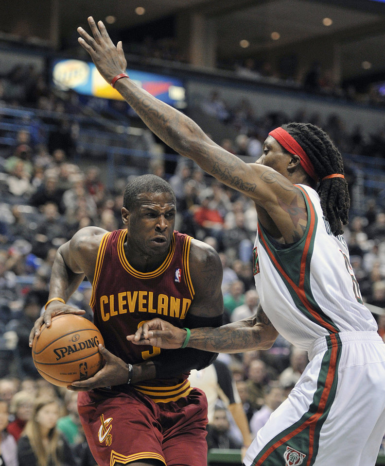 Photo - Cleveland Cavaliers' Dion Waiters left, drives to the basket around Milwaukee Bucks' Marquis Daniels during the first half of an NBA basketball game Saturday, Dec. 22, 2012, in Milwaukee. (AP Photo/Jim Prisching)