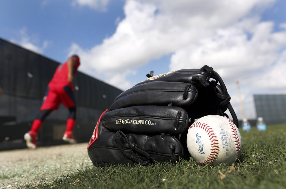 Photo - St. Louis Cardinals' Oscar Taveras jogs past his glove and a ball during an informal spring training baseball practice Wednesday, Feb. 12, 2014, in Jupiter, Fla. Cardinals pitchers and catchers first official practice is scheduled for Thursday. (AP Photo/Jeff Roberson)