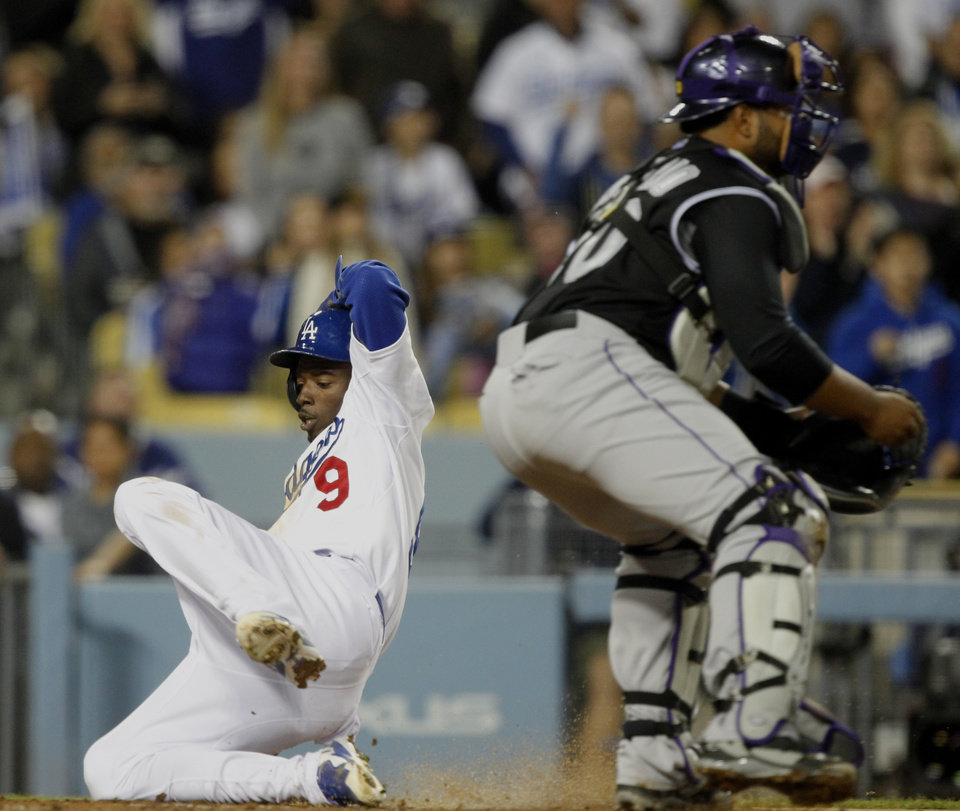 Photo - Los Angeles Dodgers' Dee Gordon (9) scores on a single to left field by Dodgers' Yasiel Puig, as the throw is cut off en route to Colorado Rockies catcher Wilin Rosario, right, in the third inning of a baseball game on Friday, April 25, 2014, in Los Angeles. (AP Photo/Alex Gallardo)