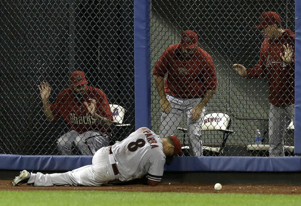 Photo - Arizona Diamondbacks' Gerardo Parra lies in the outfield after being injured while trying to catch a ball hit for a triple by New York Mets' Omar Quintanilla during the eighth inning of the baseball game at Citi Field, Monday, July 1, 2013, in New York. (AP Photo/Seth Wenig)