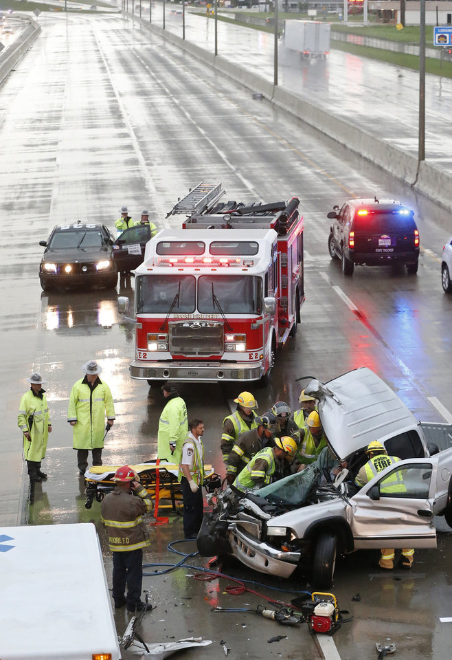 Photo - First responders work to remove a passenger of a truck involved in an accident on Interstate 35 during severe weather in Moore, Okla., Wednesday, May 6, 2015. I-35 southbound is closed behind the accident. (AP Photo/Sue Ogrocki)