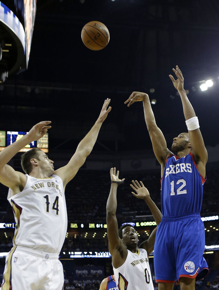 Photo - Philadelphia 76ers small forward Evan Turner (12) shoots over New Orleans Pelicans center Jason Smith (14) in the first half of an NBA basketball game in New Orleans, Saturday, Nov. 16, 2013. (AP Photo/Gerald Herbert)