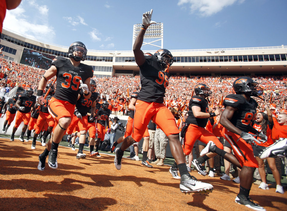 Photo - Oklahoma State runs on to the field before the first half of the college football game between the Oklahoma State University Cowboys (OSU) and the University of Kansas Jayhawks (KU) at Boone Pickens Stadium in Stillwater, Okla., Saturday, Oct. 8, 2011. Photo by Sarah Phipps, The Oklahoman