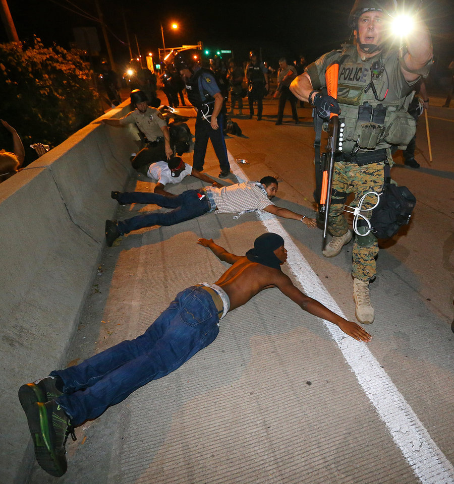 Photo - Police begin arresting dozens of protesters on West Florissant Avenue after they refused to leave the area and some began throwing objects at officers in Ferguson, Mo. early Wednesday, Aug. 20, 2014. On Aug. 9, 2014, a white police officer fatally shot Michael Brown, an unarmed black 18-year old, in the St. Louis suburb. (AP Photo/Atlanta Journal-Constitution, Curtis Compton)