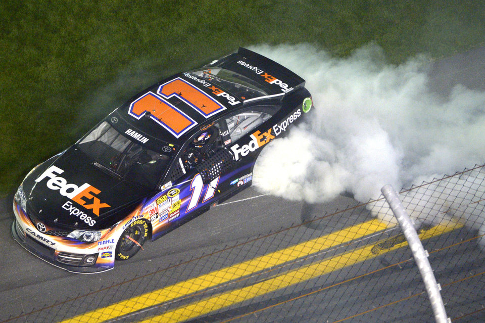 Photo - Denny  Hamlin (11) performs a burnout in front of the grandstands after winning the NASCAR Sprint Unlimited auto race at Daytona International Speedway in Daytona Beach, Fla., Saturday, Feb. 15, 2014. (AP Photo/Phelan M. Ebenhack)