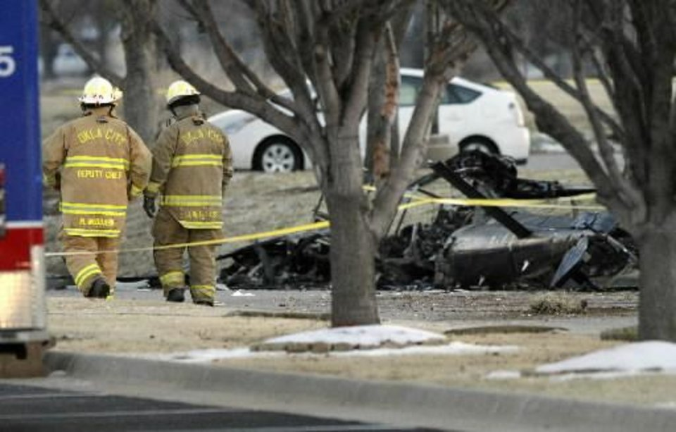Photo - Oklahoma City firefighters walk past the wreckage of a medical helicopter which crashed in front of the Saint Ann Retirement Center on Britton Road between Rockwell and Council Roads in Oklahoma City, OK, Friday, February 22, 2013. Two people were killed in the crash. By Paul Hellstern, The Oklahoman