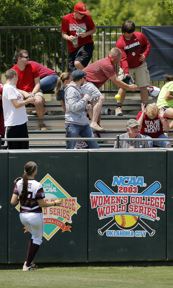 Photo - Texas A&M's Emily Albus (17) watches fans try to catch a home run ball by OU's Lauren Chamberlain (44) in the 4th inning during the final game of the Norman Regional in 2014 NCAA softball championship between Oklahoma and Texas A&M in Norman, Okla., Sunday, May 18, 2014. OU won 11-6. Photo by Nate Billings, The Oklahoman