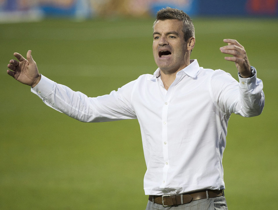 Photo - Toronto FC head coach Ryan Nelsen argues a call with one of the officials while playing against Sporting Kansas City during second-half MLS soccer game action in Toronto, Saturday, July 26, 2014. (AP Photo/The Canadian Press, Nathan Denette)
