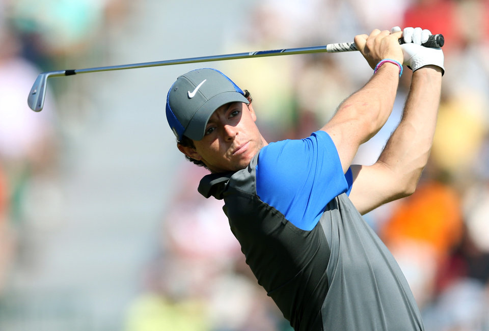 Photo - Rory McIlroy of Northern Ireland plays a shot off the 4th tee during the first day of the British Open Golf championship at the Royal Liverpool golf club, Hoylake, England, Thursday July 17, 2014. (AP Photo/Scott Heppell)