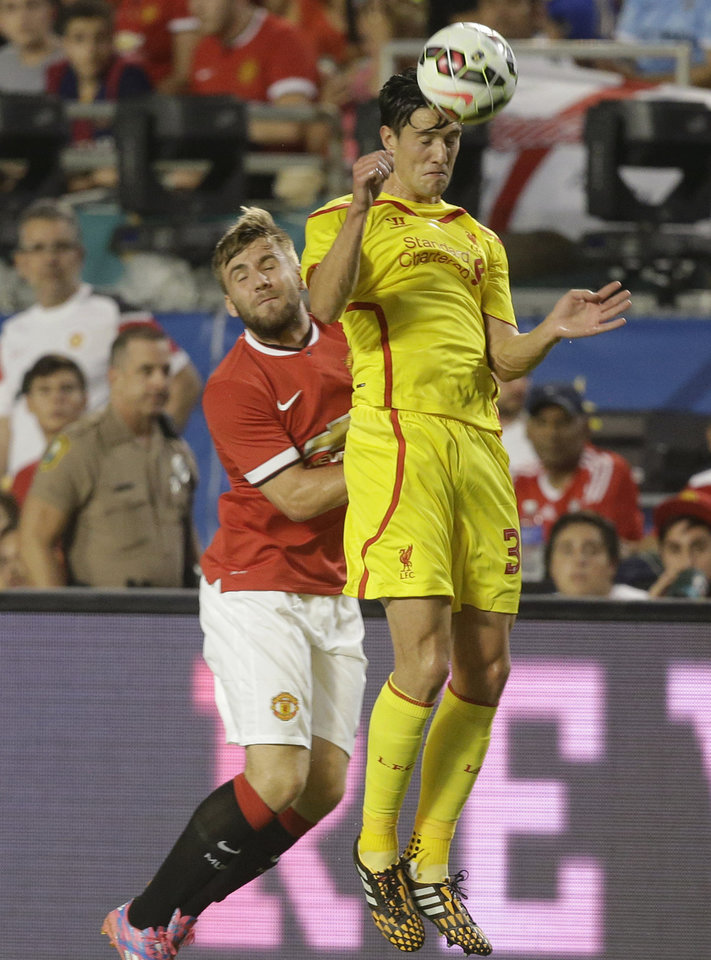 Photo - Liverpool's Martin Kelly, right, heads the ball against Manchester United's Luke Shaw, left, in the first half during the final of the Guinness International Champions Cup soccer match, Monday, Aug. 4,  2014, in Miami Gardens, Fla. (AP Photo/Lynne Sladky)